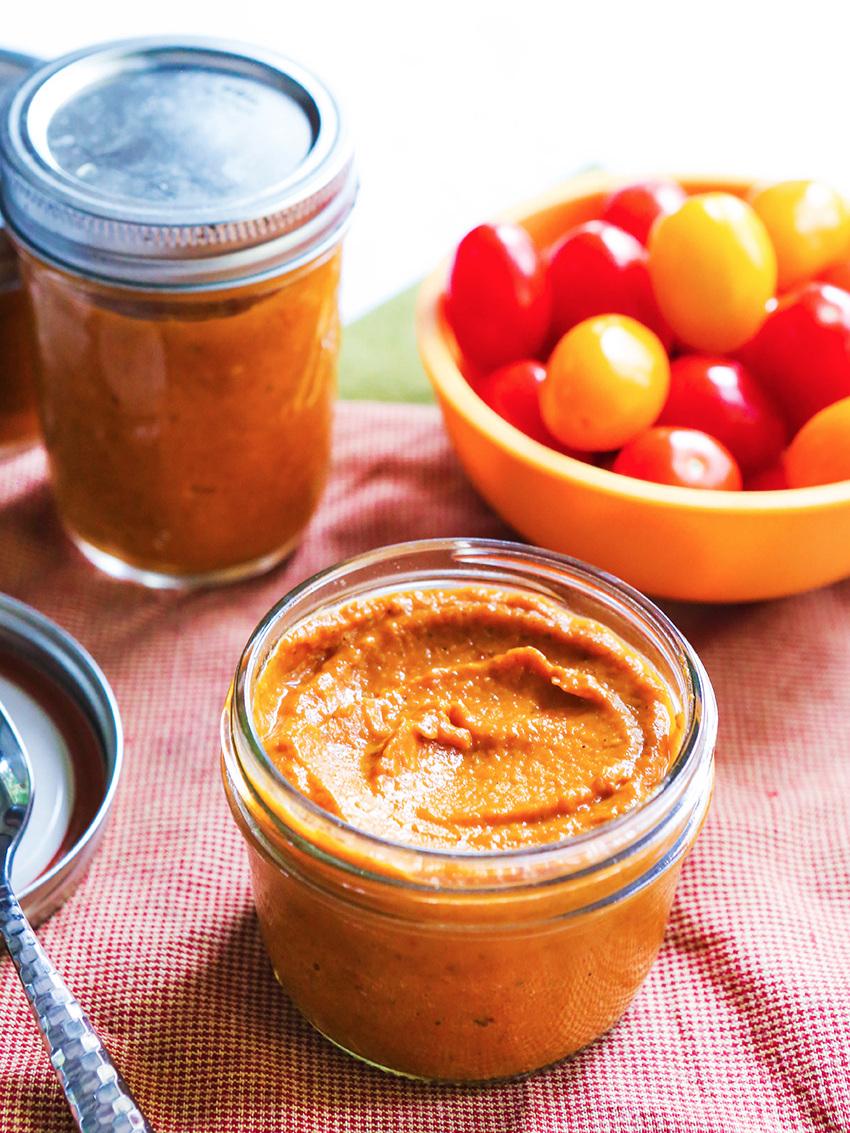 Open jar of homemade tomato sauce next to cherry tomatoes