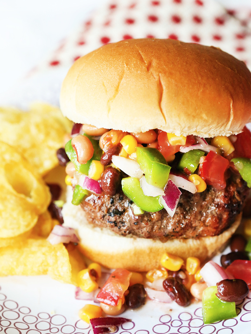 burger in a bun with colorful salsa spilling out sitting next to a pile of chips