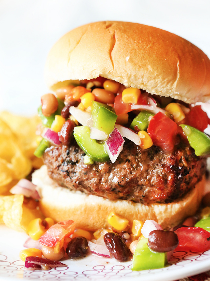 side shot of a burger piled high with bean salsa sitting on a plate