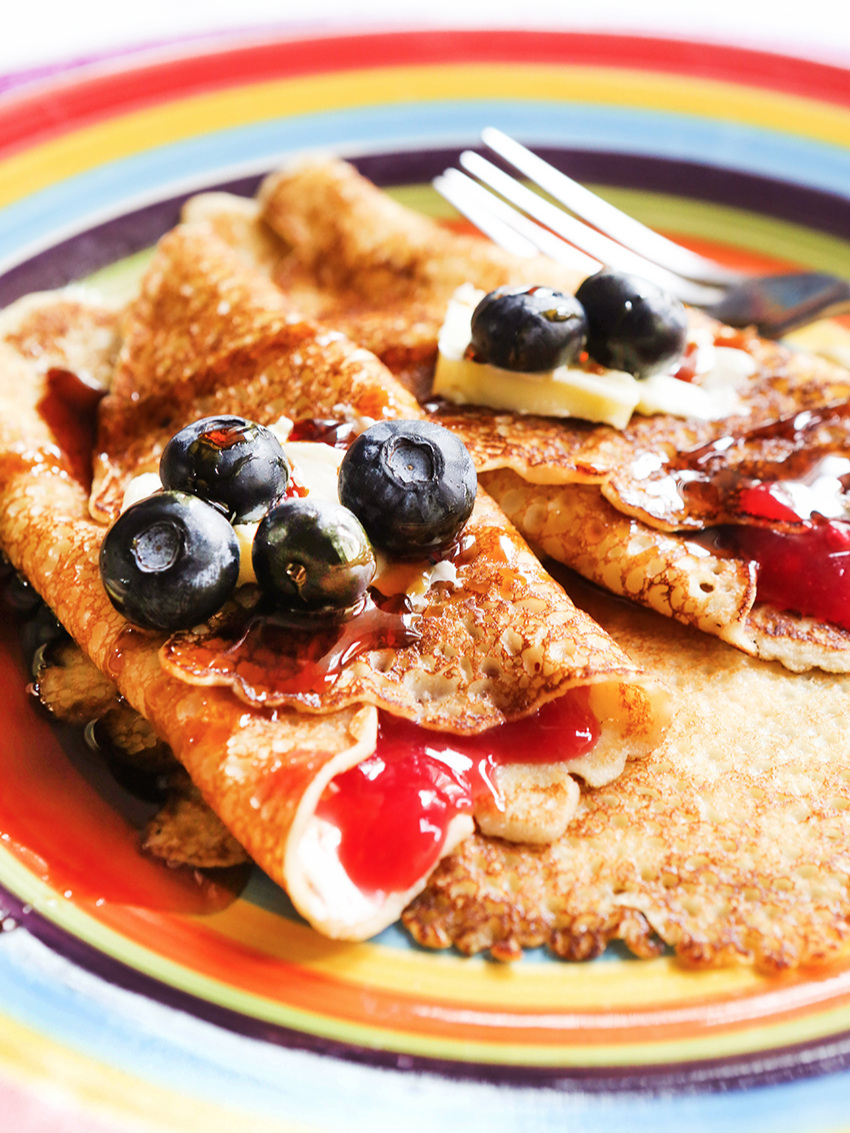 swedish pancakes rolled up on a colorful plate with blueberries on top