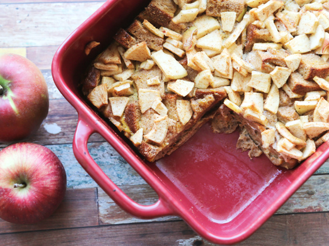 Baked apple french toast in a casserole dish with a slice missing