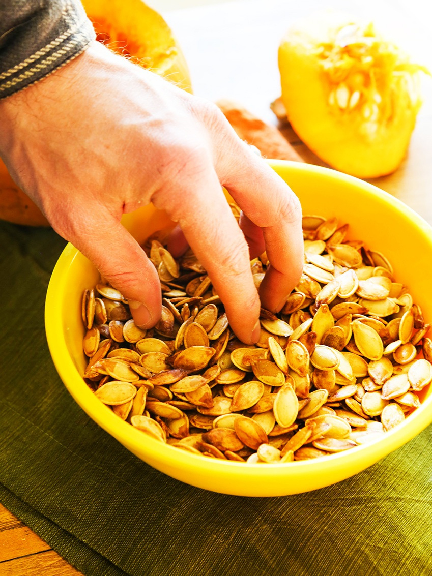 hand in a bowl ready to scoop up pumpkin seeds