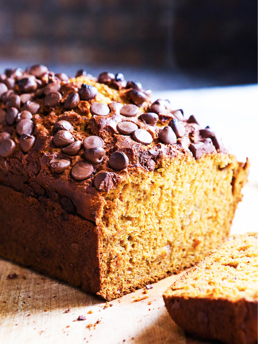 loaf of pumpkin banana bread with chocolate chips and slice removed