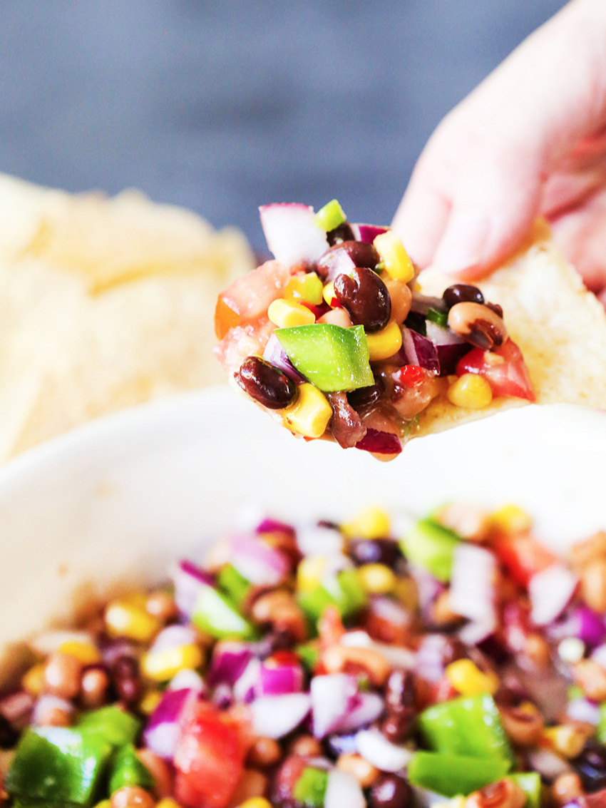 fingers holding chip full of chunky salsa over serving bowl