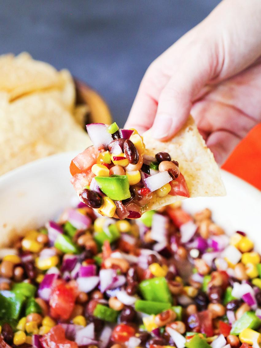 hand holding chip full of salsa over salsa bowl