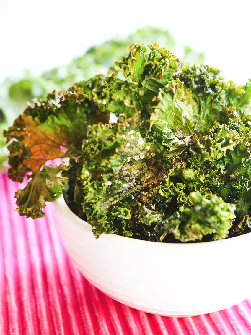 Bowl full of crispy kale with fresh uncooked kale on the side