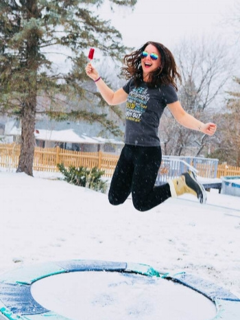 crazy girl with popsicle jumping on a trampoline with snow