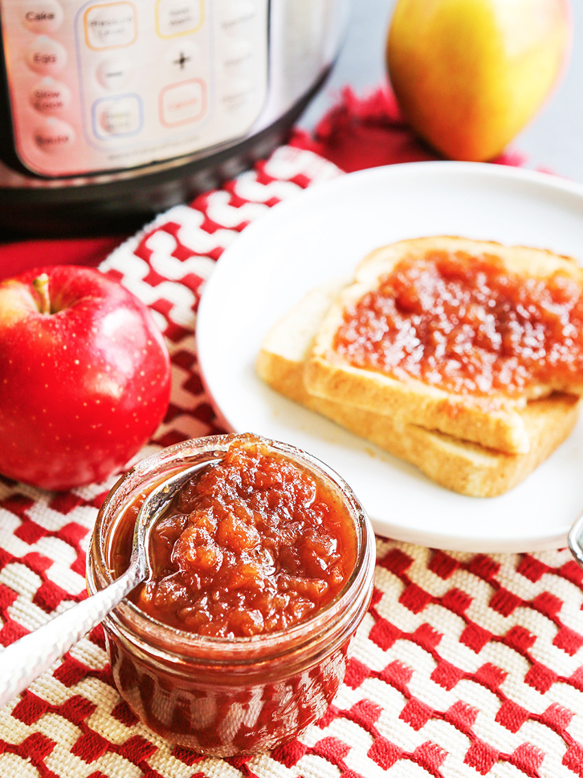 spoon in a small mason jar of apple butter with jam smeared on a piece of toast in the background