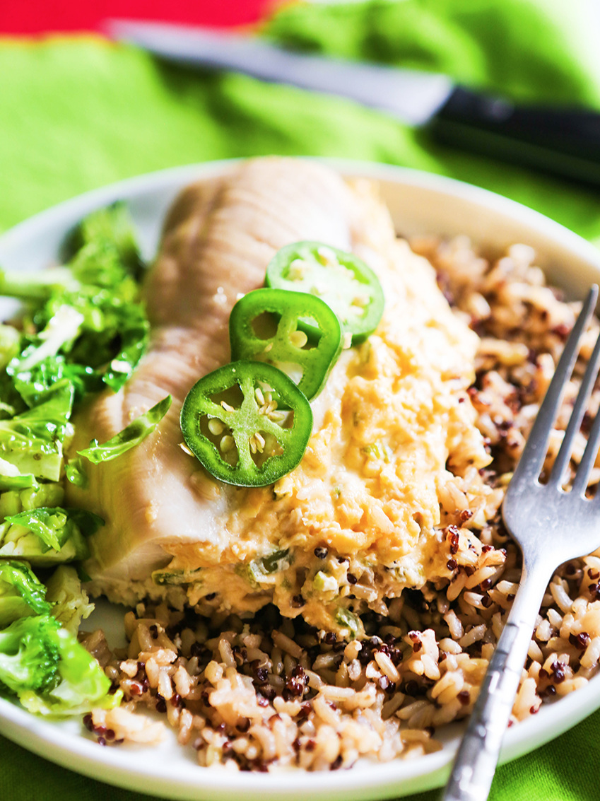 jalapeon stuffed chicken breast over a bed of rice and with jalapeno slices on top