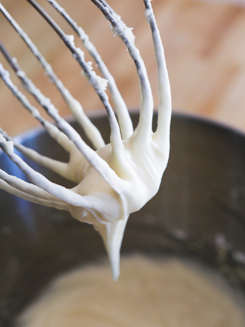 cream cheese frosting dripping off a stand mixer whisk attachment