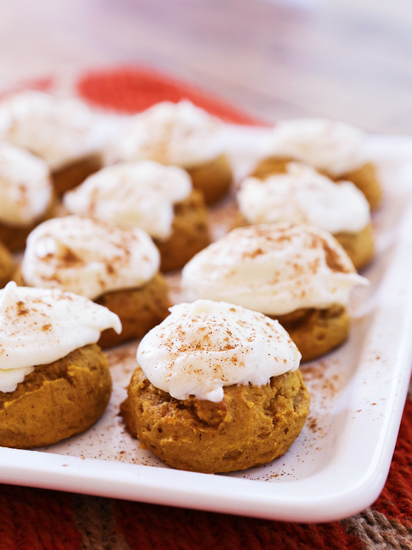 platter of perfectly lined up pumpkin cookies and frosting on top