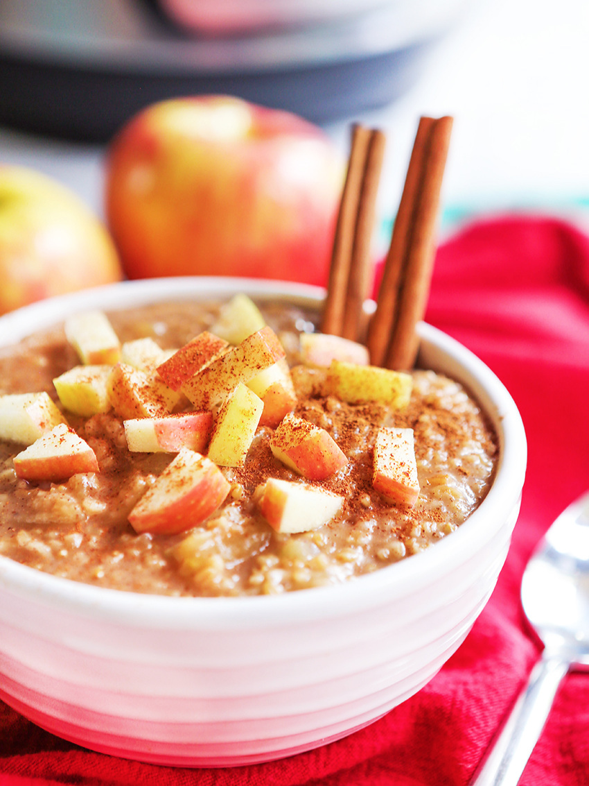 Prepared bowl of instant pot apple oatmeal with two cinnamon sticks sticking out