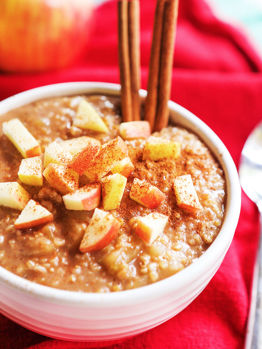 Bowl of apple cinnamon oatmeal with 2 cinnamon sticks inserted into the bowl