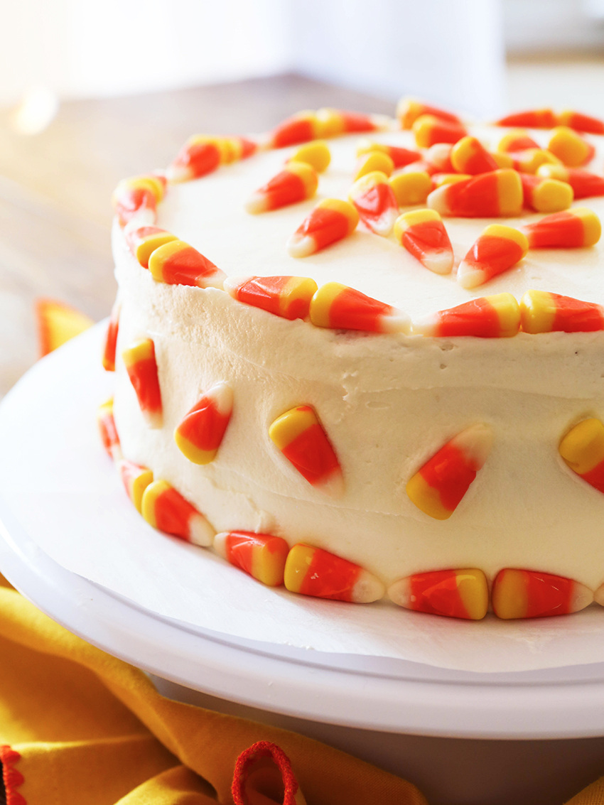finished cake topped with candy corn on a white cake plate