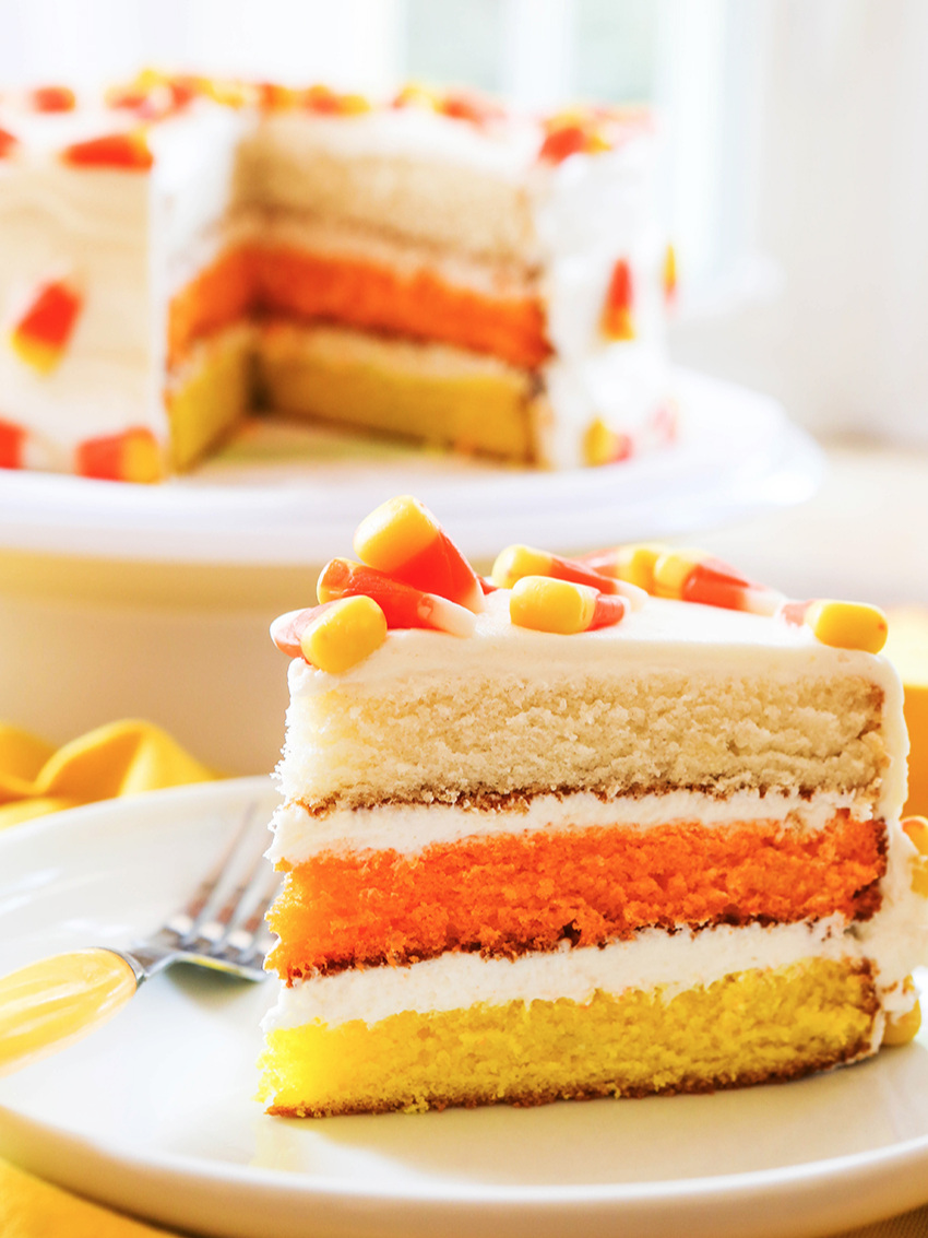 perfect slice of candy corn cake sitting next to cake stand