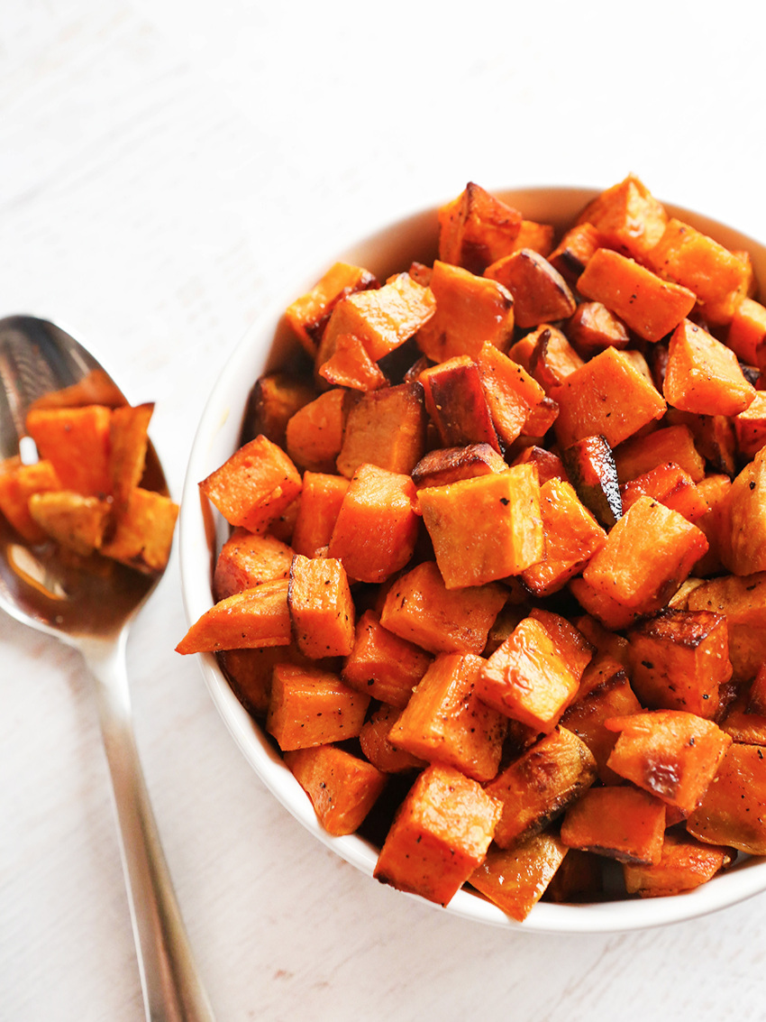 Bowl of sweet potatoes with spoon next to it