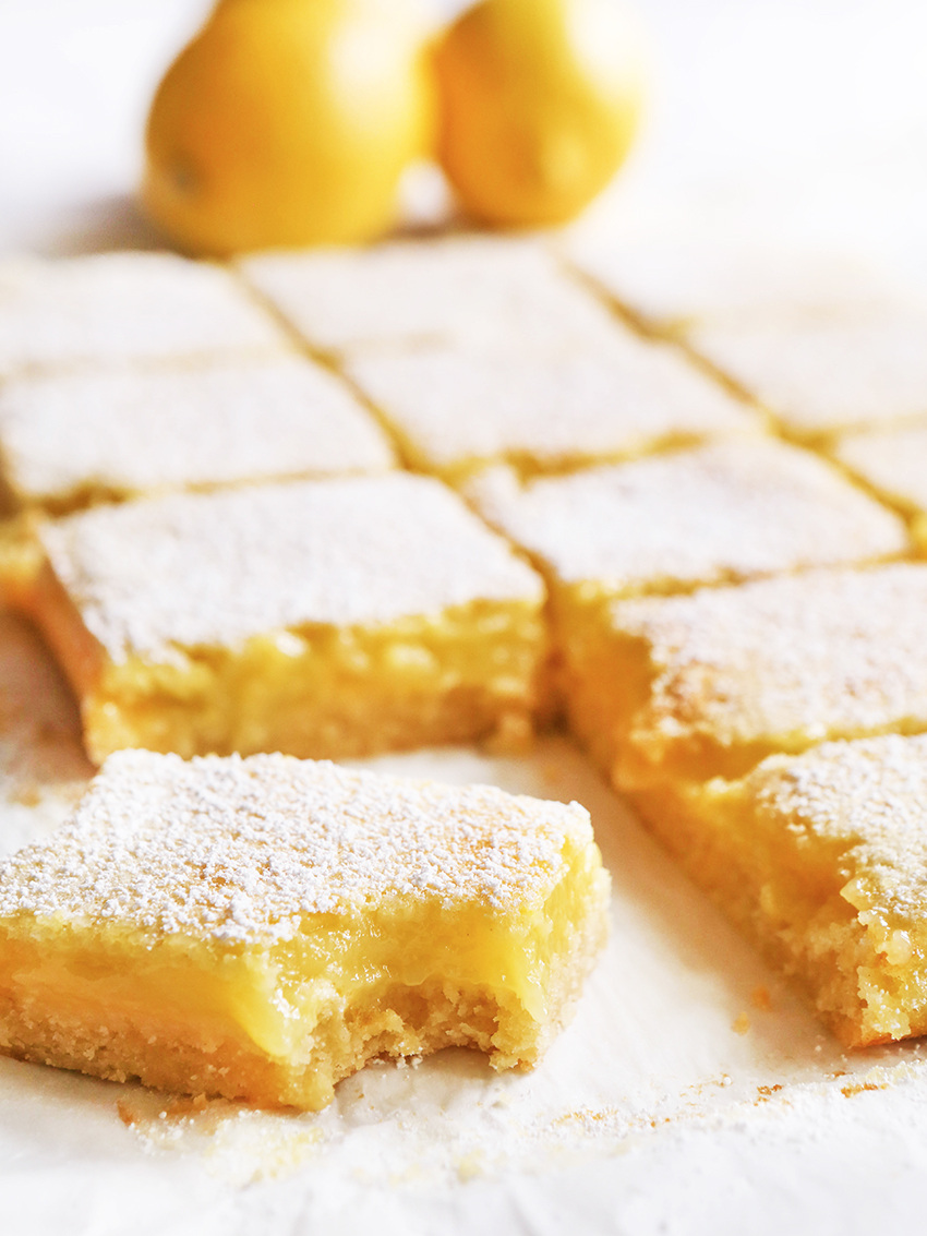 Lemon bars on parchment paper sliced into squares with one bar moved to the front with a bite taken out of it