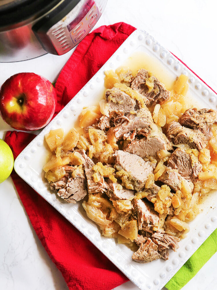Platter of pork and apples sitting next to an Instant Pot