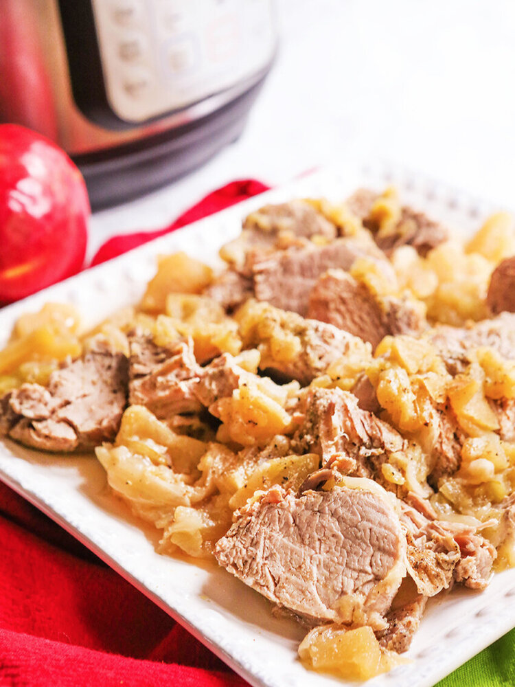 Serving platter with pork and apples sitting by Instant Pot