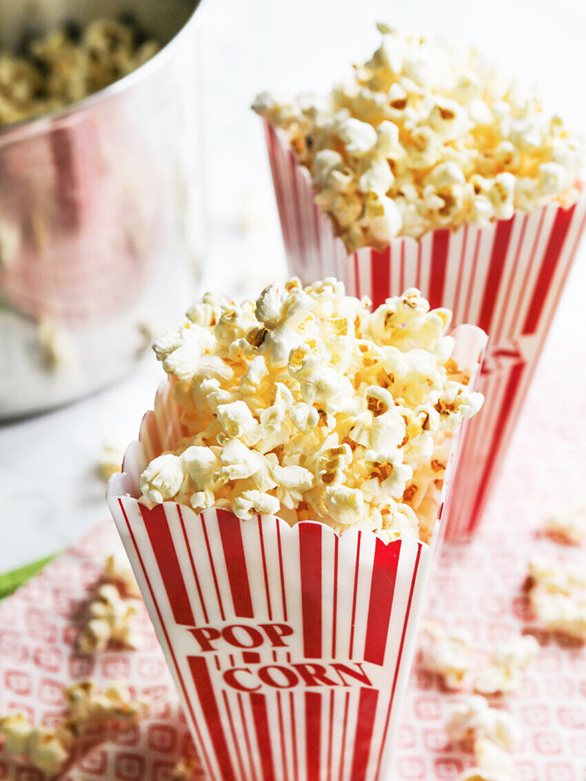 Overflowing stovetop popcorn in red and white box with popcorn kernels on table