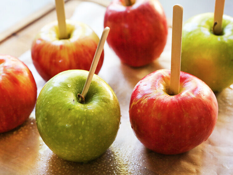Popsicle sticks jabbed into apples on a cutting board