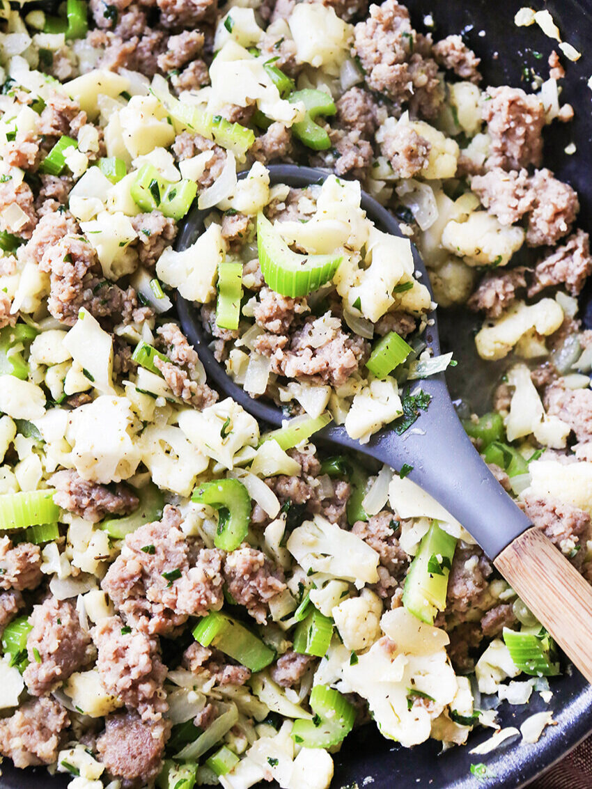 close up of cauliflower stuffing in pan with serving spoon