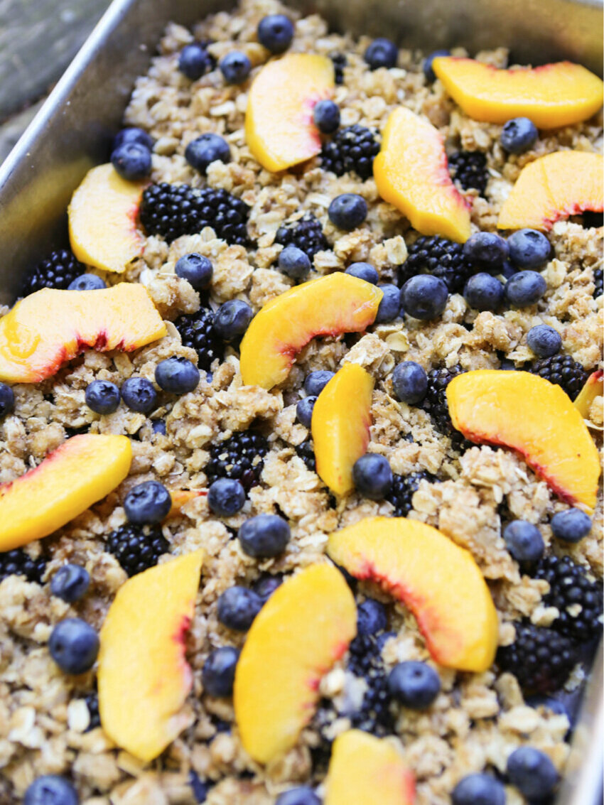 pan of unbaked fruit crisp with sliced peaches, blueberries and blackberries