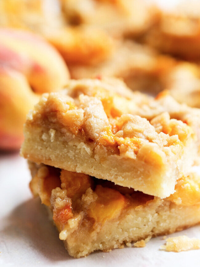 two square peach crumb bars sitting on one another