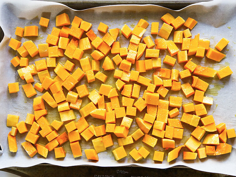 Butternut squash on baking sheet with olive oil