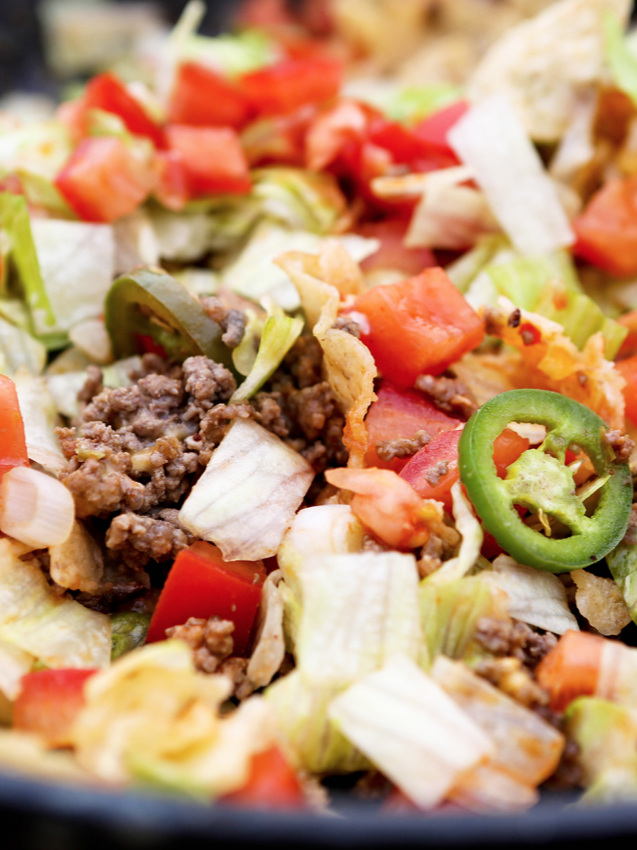 Close up of campfire nachos focusing on jalapeno slice