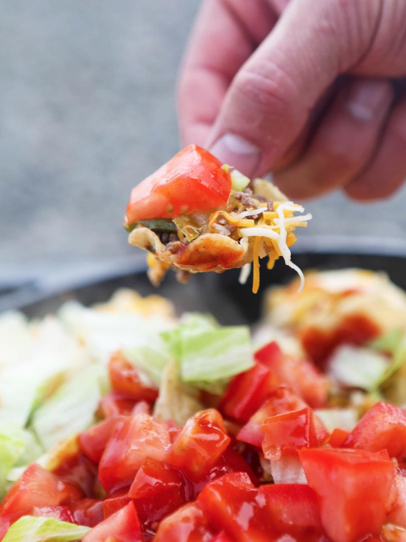 Hand holding chip full of nachos