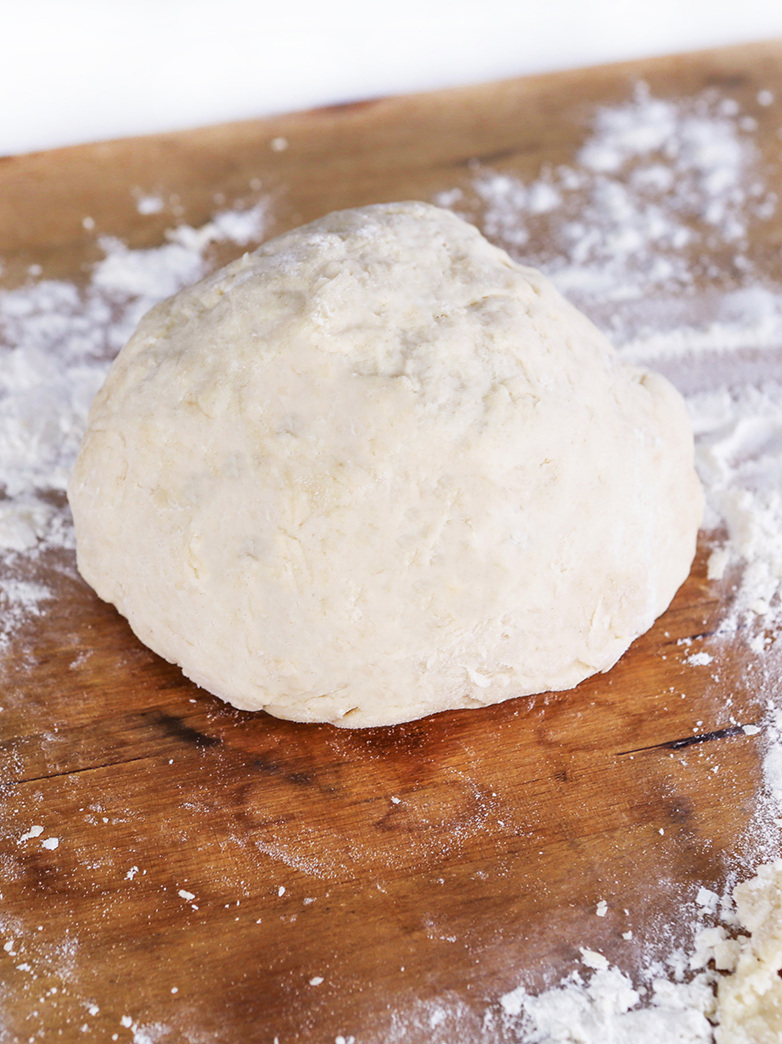 Blob of pizza dough on cutting board, ready for rolling