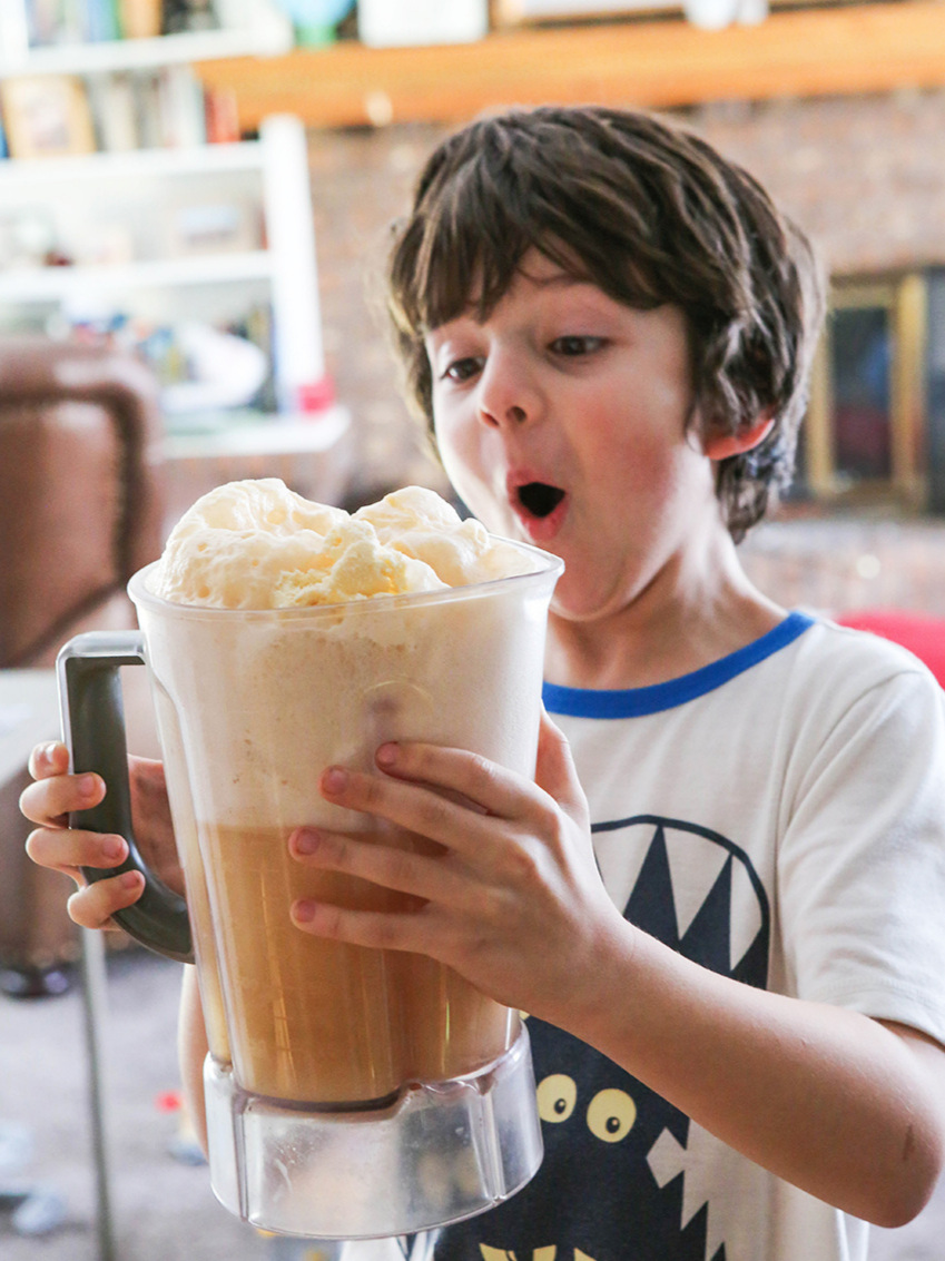 Cute boy in awe and holding a pitcher filled with butterbeer