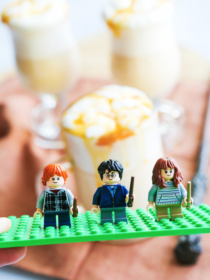 Lego figures of Ron, Harry and Hermione in front of glasses of Butterbeer