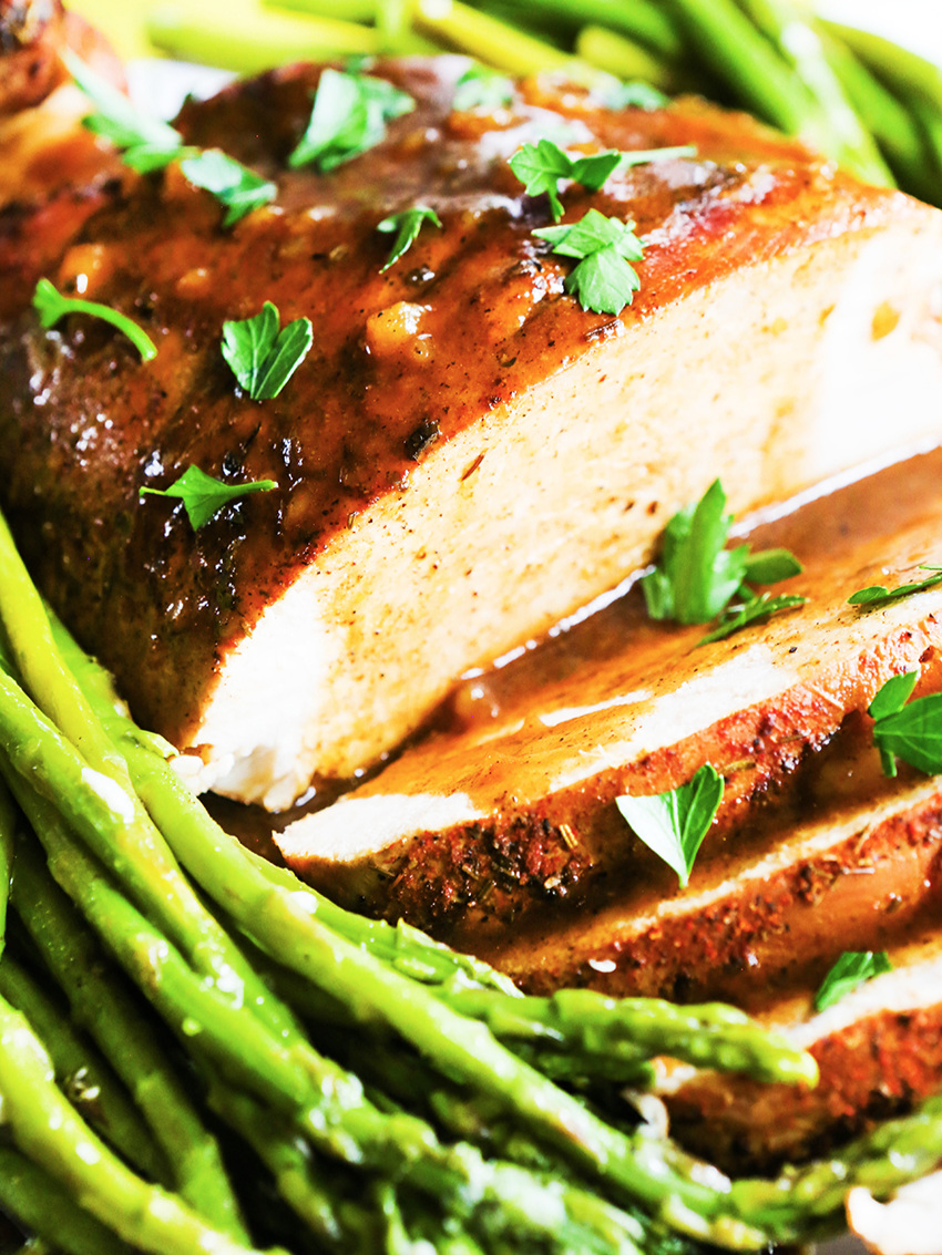 Close up of turkey breast with gravy and asparagus