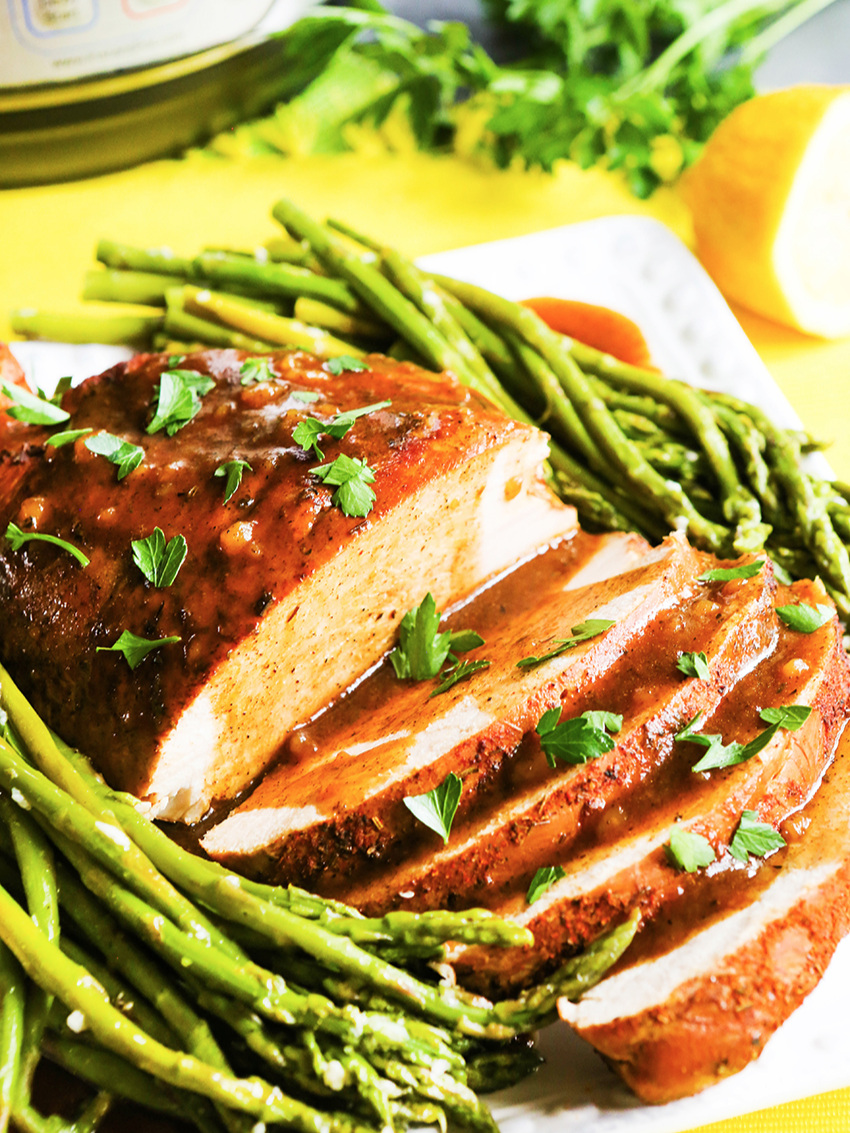 Turkey on platter with asparagus next to pressure cooker