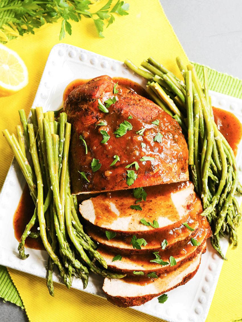 Top view of sliced turkey breast on plate with asparagus