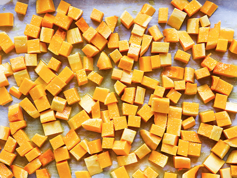 Pan of butternut squash chunks with olive oil and salt