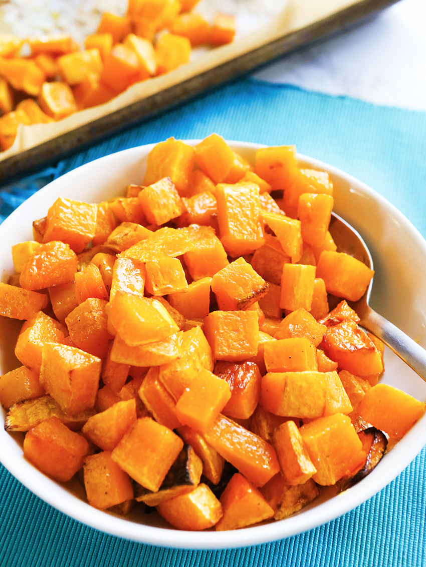 Bowl of roasted squash with pan in background