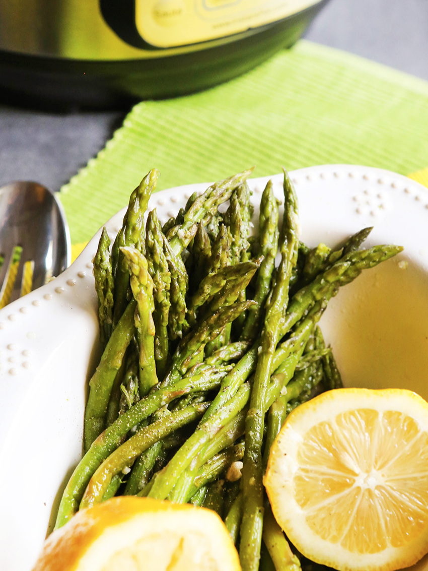 Asparagus in bowl with lemons sitting next to Instant Pot