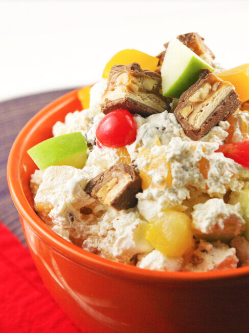 Orange bowl of snickers fruit salad with whipped cream