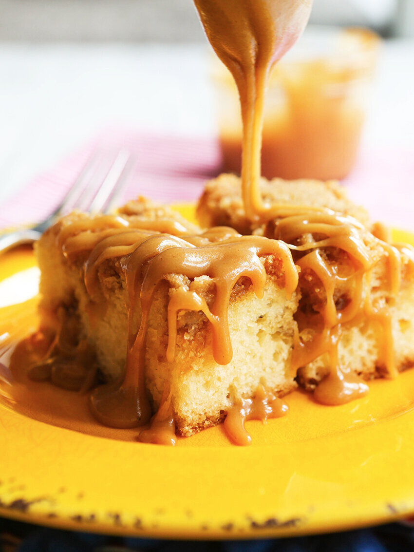 Salted caramel sauce being drizzled over piece of coffee cake