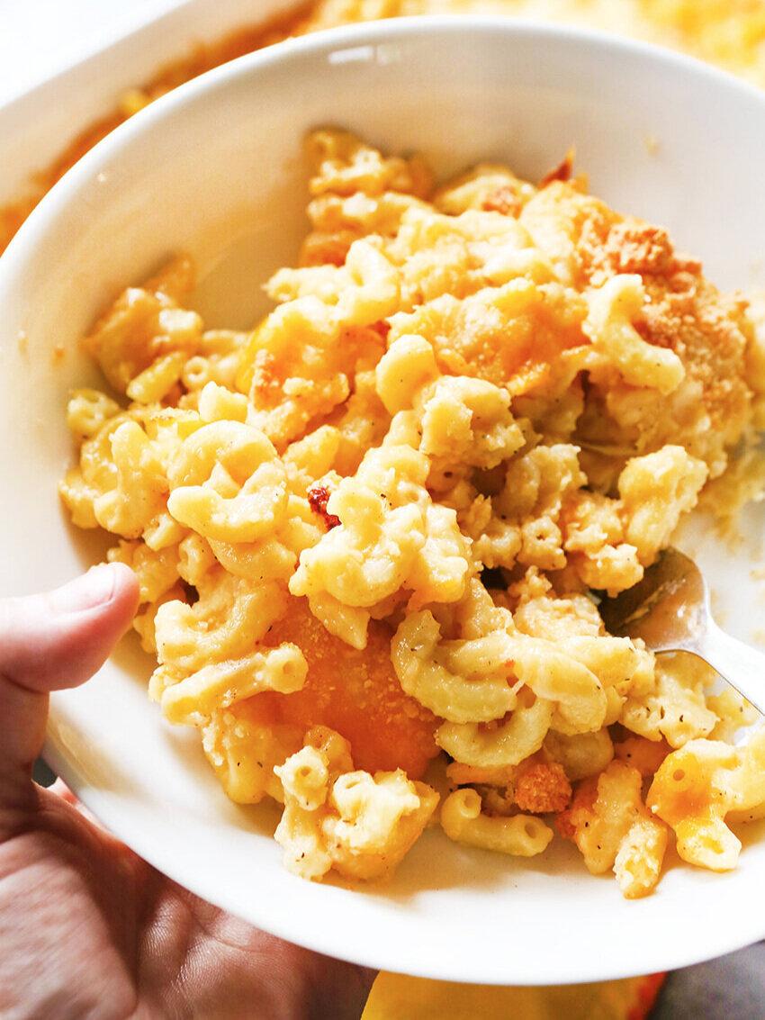 Hand holding bowl full of dreamy cheesy pasta