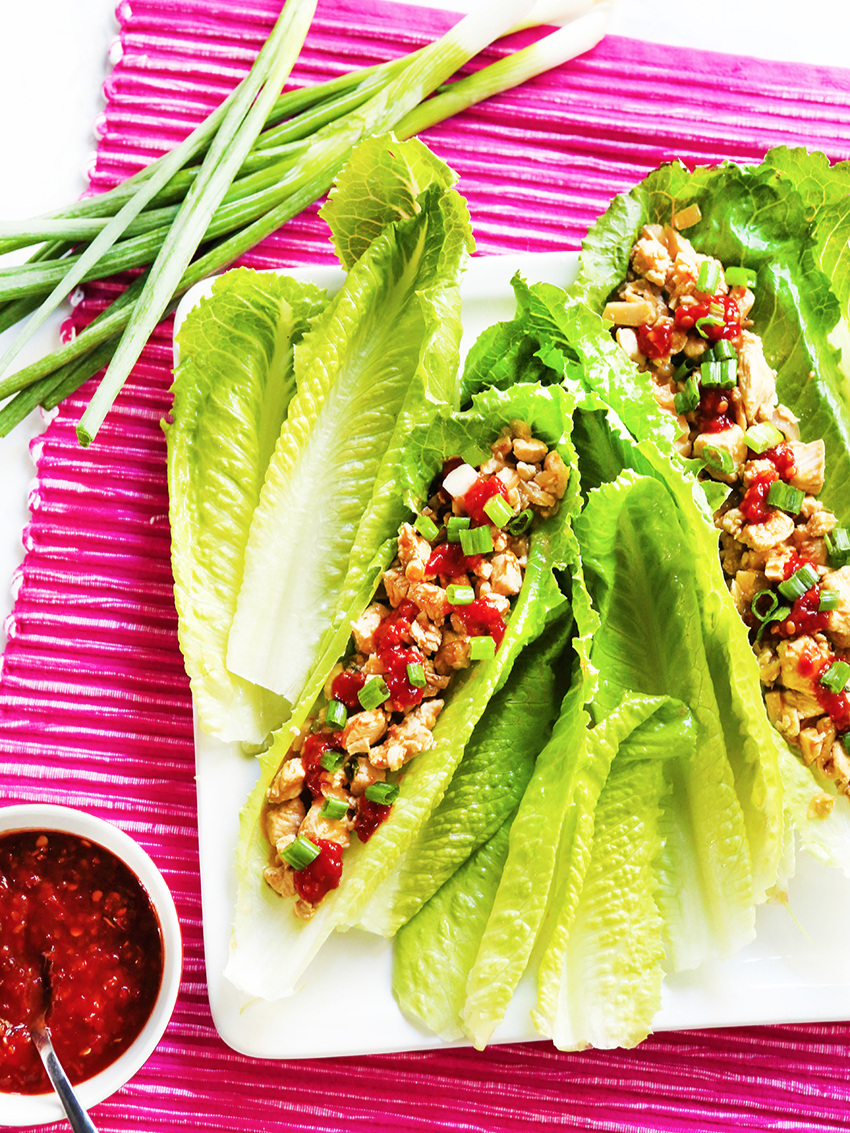 Serving plate with two chicken lettuce wraps and empty lettuce leaves