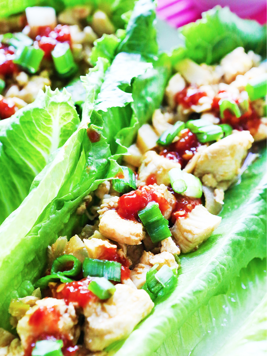 Close up of chicken lettuce wrap with chili sauce drizzled over