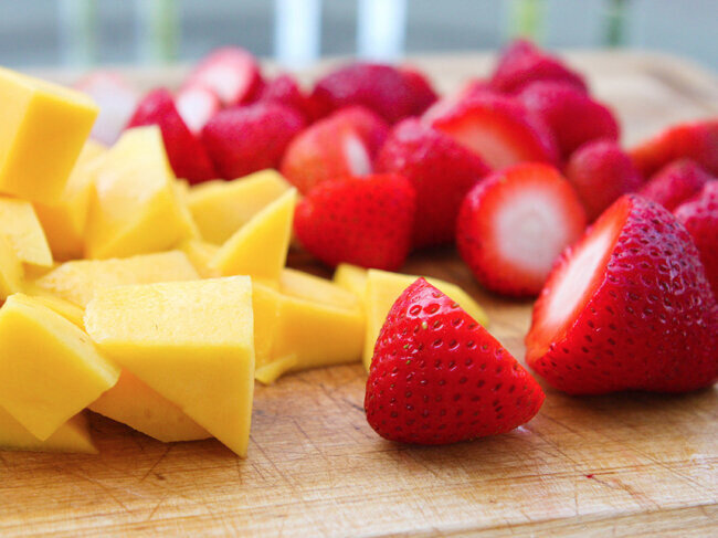 Chopped mango and strawberry pieces on a cutting board