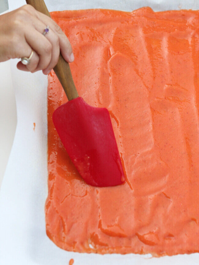 Smoothing fruit puree with a spatula in baking pan