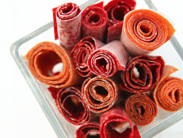 Square glass dish filled with rolled fruit roll ups