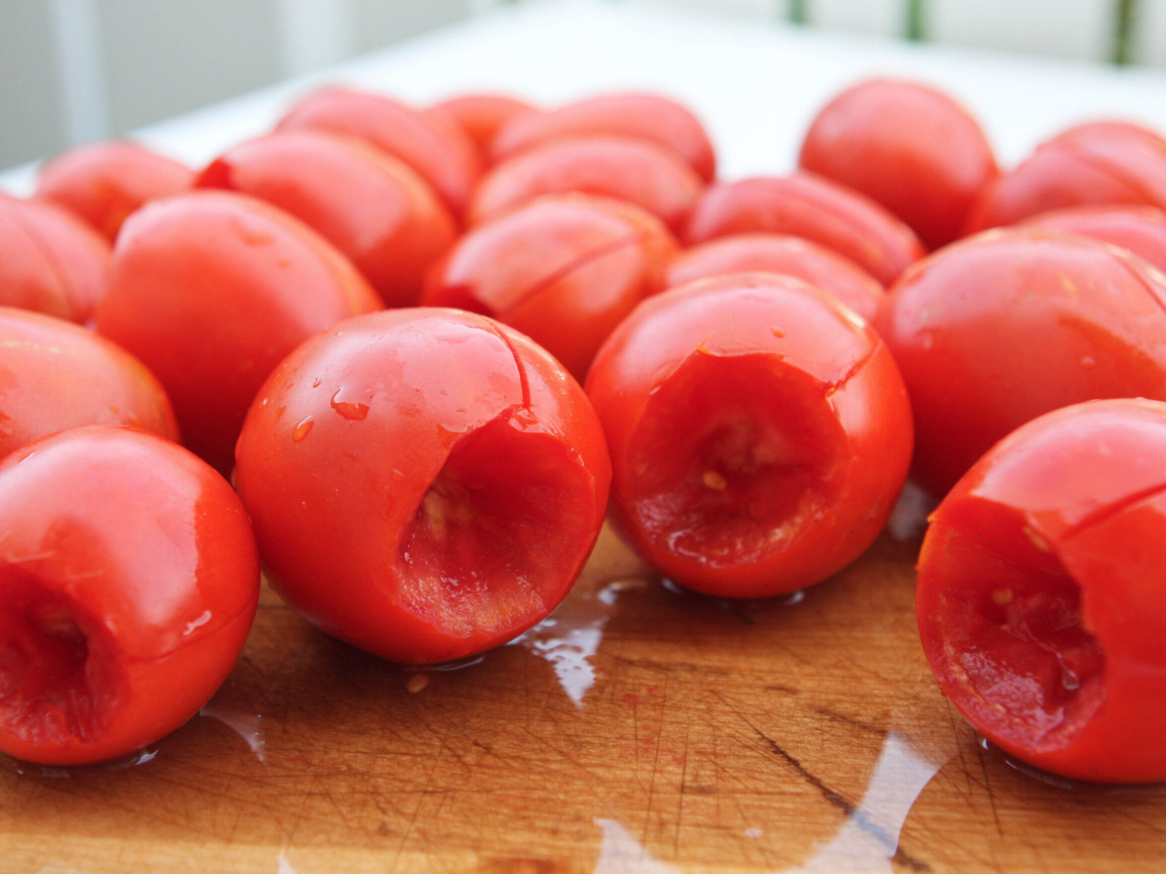 Roma tomatoes on a cutting board, ready for freezing