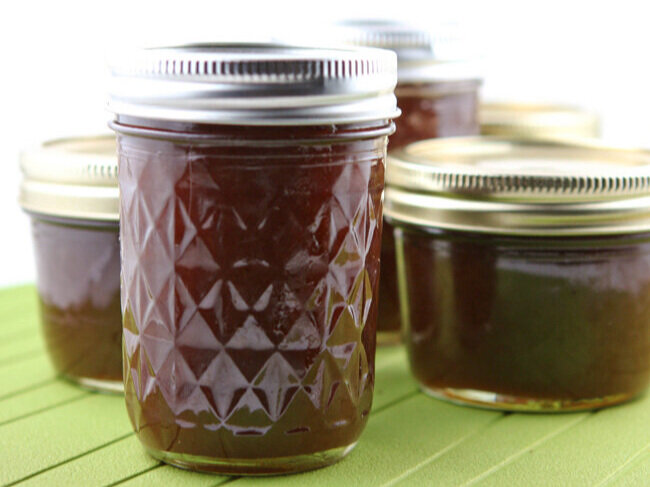 Jars filled with apple butter on a green placemat